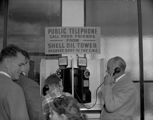 CNE Guests Lining Up To Use The Public Telephone, 1955